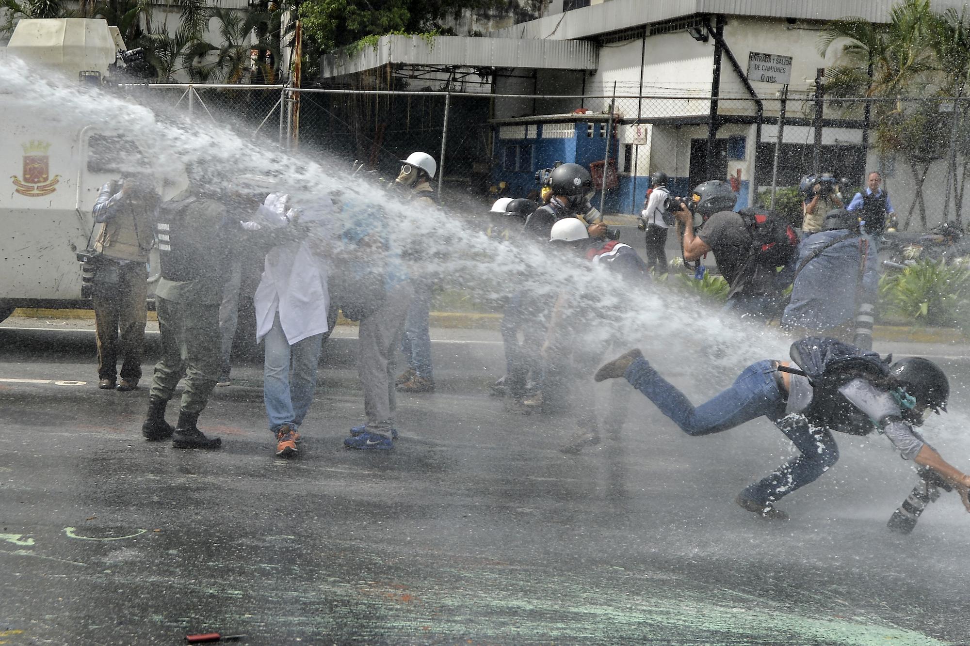 La photographe de AP Ariana Cubillos est attaquée par un canon à eau pendant une manifestation à Caracas, le 22 mai 2017. LUIS ROBAYO / AFP